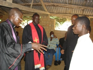 Director of Disciples AIDS office Rev. Alain Lokalamba assists in receiving the confession of faith of two youth in a rural parish