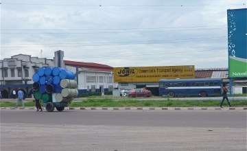 """One man pushes 18 empty oil drums on a """"pousse pousse"""" cart down a Kinshasa street."""