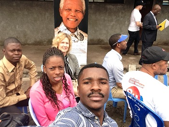 """Ms. Linda James in back of UPC students on the campus.  """"Education is the most powerful weapon you can use to change the world."""" - Nelson Mandela"""
